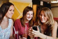 谈话和微笑在咖啡馆的朋友 免版税库存照片