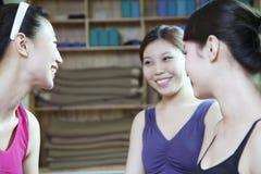 谈话和微笑在瑜伽演播室的三个朋友 库存照片