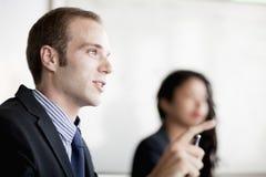 谈话和打手势在业务会议上的商人 图库摄影