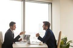 谈话和研究膝上型计算机的两个伙伴业务会议  库存照片