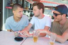 谈话和笑在咖啡大阳台的三个愉快的朋友 库存图片