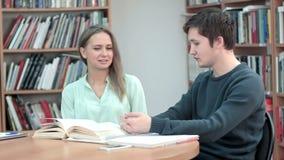 谈话和笑在好书的两个最好的朋友在图书馆里 股票录像