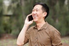 谈话和笑在电话的年轻亚裔人 免版税图库摄影