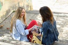 谈话和笑在都市步的两个少妇 免版税库存照片