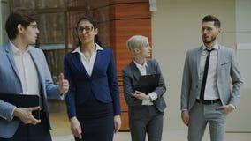 谈话和走在办公室大厅的小组年轻商人 股票视频