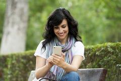 谈话和texing在她巧妙的电话的愉快的可爱的拉丁妇女 免版税库存图片
