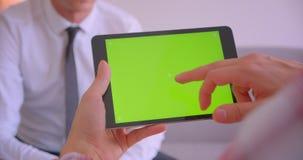 谈话商人特写镜头的画象与有绿色色度关键屏幕的片剂合作在办公室 股票视频