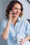 谈话在一个手机和拿着杯子的俏丽的微笑的妇女 库存照片