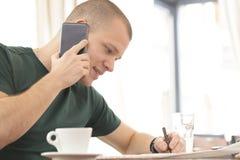 谈话在一个手机和寻找他自己的一个工作 免版税库存图片