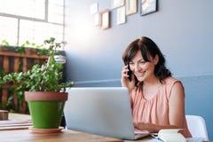 谈话在她的手机和使用膝上型计算机的年轻女实业家 免版税库存照片