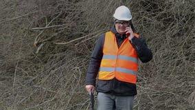 谈话在巧妙的电话和走在堆的伐木工人分支附近 股票视频