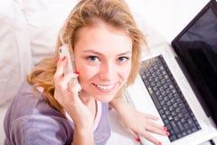 谈话在巧妙的电话,运转在膝上型计算机可爱的愉快的微笑的年轻女商人在床上在睡衣 图库摄影