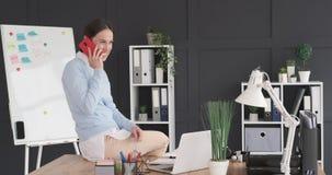 谈话在手机和使用膝上型计算机的女实业家在办公室 股票视频