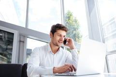 谈话在手机和使用膝上型计算机的愉快的年轻商人 免版税库存图片