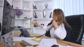 谈话在手机和做在笔记本的年轻女商人笔记,当坐在桌上在办公室时 股票视频