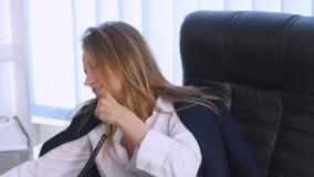 谈话在手机和做在笔记本的年轻女商人笔记,当坐在桌上在办公室时 影视素材