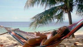 谈话在手机和放松在热带海滩的吊床的可爱的愉快的妇女在棕榈树旁边和美丽 股票视频