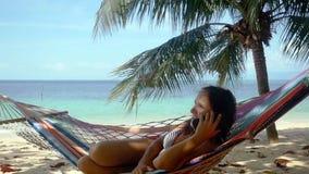 谈话在手机和放松在热带海滩的吊床的可爱的深色的妇女在棕榈树旁边和美丽 股票视频