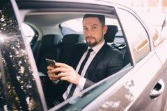 谈话在手机和看窗口外的商人,当坐汽车时后座  公商业主管 免版税库存照片