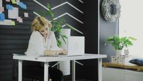 谈话在手机和研究计算机的繁忙的女商人在办公室 股票视频