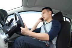 谈话在手机,当驾驶时 免版税图库摄影