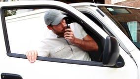 谈话在携带无线电话和进入搬运车的交付司机 股票录像