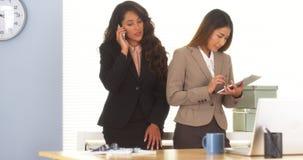 谈话在智能手机和使用片剂的两个混合的族种同事 免版税图库摄影