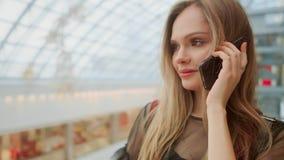 谈话在智能手机和坐与在购物中心的购物带来的美女 股票录像