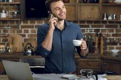 谈话在智能手机和拿着咖啡杯的年轻人 免版税库存图片