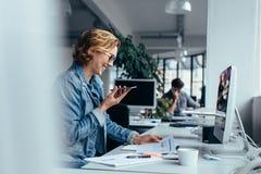 谈话在智能手机和看文件的女实业家 免版税库存照片