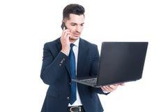 谈话在智能手机和研究膝上型计算机的英俊的商人 免版税库存图片
