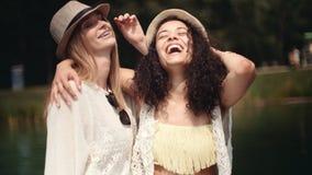 谈话在湖附近和享受假期的美丽的年轻混合的族种女孩 免版税库存照片