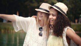 谈话在湖附近和享受假期的美丽的年轻混合的族种女孩 免版税库存图片