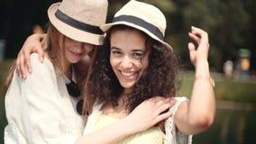 谈话在湖附近和享受假期的美丽的年轻混合的族种女孩 免版税图库摄影