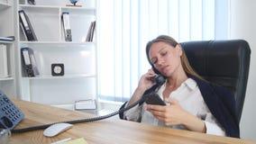 谈话在电话和使用智能手机的年轻可爱的女实业家在办公室和微笑 影视素材