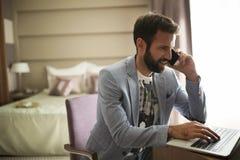 谈话在电话和使用膝上型计算机的年轻成功的商人的图片 免版税库存照片