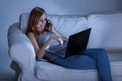 谈话在电话和使用膝上型计算机 免版税库存照片