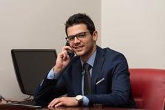 谈话在电话和使用计算机的商人 免版税库存照片