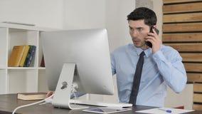 谈话在电话和使用计算机的年轻商人 股票录像