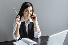 谈话在电话和做在一个笔记本的年轻女商人笔记在办公室 库存图片