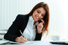 谈话在电话和写笔记的女实业家 免版税图库摄影