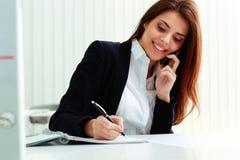 谈话在电话和写笔记的年轻快乐的女实业家 免版税图库摄影