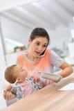 谈话在电话和喂养她的婴孩的繁忙的妇女 免版税图库摄影