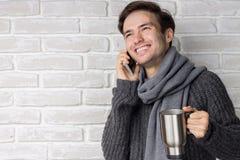谈话在电话和喝一份温暖的饮料的一个愉快的人 库存图片