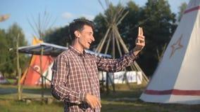 谈话在电话和微笑在背景圆锥形帐蓬/帐篷当地印地安房子的年轻人游人 帽子旅客的人在su 股票录像