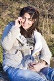 谈话在电话和拥抱她的狗的美丽的妇女画象 免版税库存图片