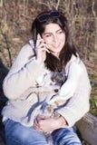谈话在电话和拥抱她的狗的美丽的妇女画象 免版税图库摄影