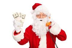 谈话在电话和拿着金钱的圣诞老人 库存照片