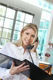 谈话在电话和检查外形的美丽的办公室夫人 免版税库存图片
