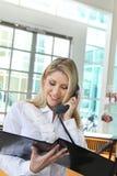 谈话在电话和检查外形的美丽的办公室夫人 图库摄影